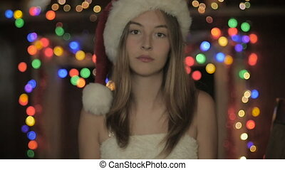 A sad young woman wearing a Christmas hat looking bored