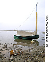 A cat boat rests in shallow water at Brewster, Cape Cod, Massachusetts