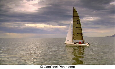 A sailboat sails on a lake with clouds above