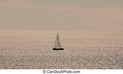 A sailboat, yacht on the horizon in sunset