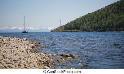 A sailing boat moves away from pebbly shore in background of a chain of mountains and steep forest.