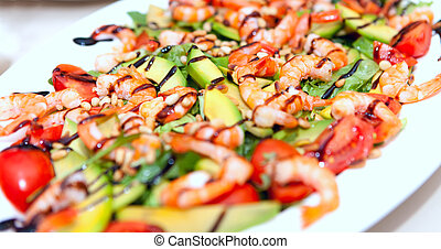 A salad dish with prawns, avocado, seafood, tomatoes in a white dish