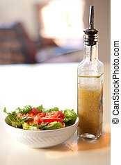 a green salad on a white table with a bottle of salad dressing