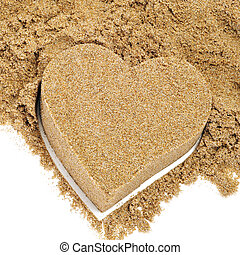 a sand heart and a pile of sand on a white background