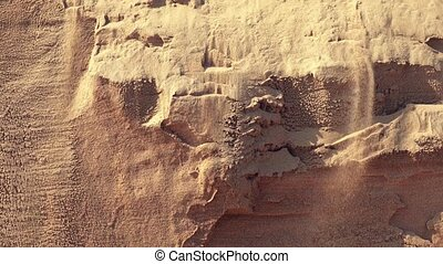 A sandfall runs down the face of a sand dune - As a sand...