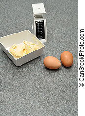 A scale, butter and eggs on a worktop in the kitchen