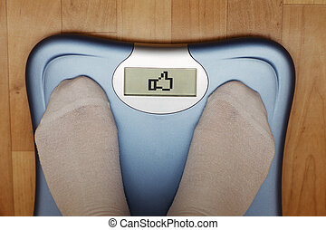 A scale with two feet of the person standing on it on a...