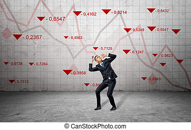 A scared businessman cowers near a concrete wall with red stock market indexes and falling statistic lines.
