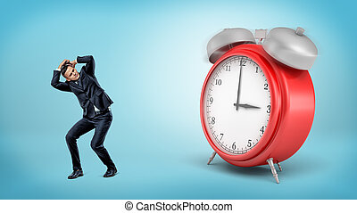 A scared businessman hides away from a giant red alarm clock standing on blue background.