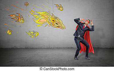A scared businessman in a superhero cape cowering under an attack of yellow paper comets on concrete background.