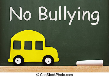 A school bus and chalk on a chalkboard with words no bullying, No bullying allowed