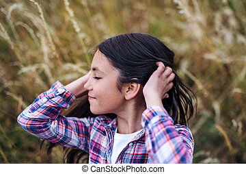 A school child standing on field trip in nature, headshot. Copy space.
