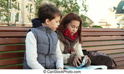 A school girl and her friend sit on a bench and examine the camera