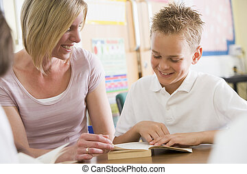 A schoolboy and his teacher reading a book in class