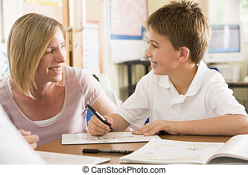 A schoolboy sitting with his teacher in class