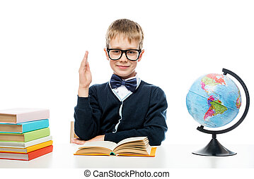 a schoolboy with glasses at a table with books and a globe pulls his hand to answer