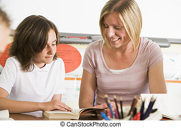 A schoolgirl and her teacher reading a book in class