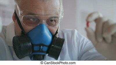 A scientist at a pharmaceutical company a drug developer wearing a blue respirator and safety glasses holds a new medicine a red pill and looks at it. High quality 4k footage
