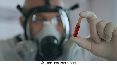A scientist doctor at a pharmaceutical company developing a drug in a laboratory in a glass respirator screen holds a new medicine a red amulet with a vaccine against the virus and looks at it. High quality 4k footage
