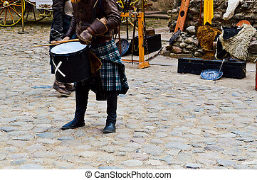 A Scottish warrior, soldier, musician in traditional costume with a skirt beats the drum on the square of a medieval old castle.