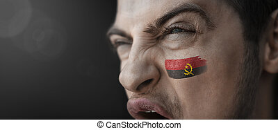 A screaming man with the image of the Angola national flag on his face