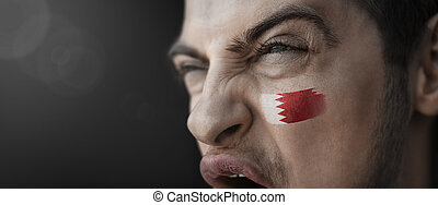 A screaming man with the image of the Bahrain national flag on his face