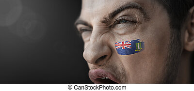 A screaming man with the image of the British Virgin Islands national flag on his face
