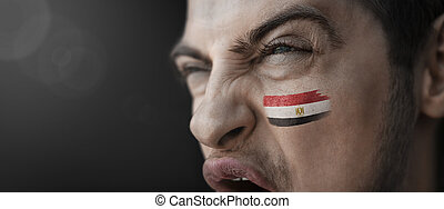 A screaming man with the image of the Egypt national flag on his face
