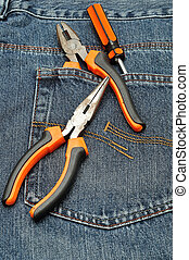 A screw driver, long nose pliers and set of pliers in the back pocket of a denim jeans pant