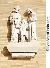 A sculpture of the Holy Family against a brick fa?ade