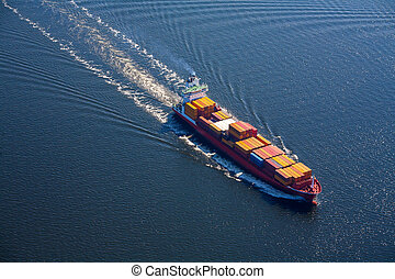 A sea vessel is a container ship at full speed in the open sea. View from above.