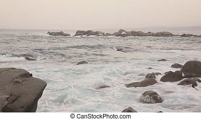 A sea wave crashing against boulders during a storm....