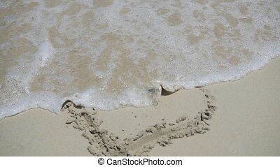 A sea wave is washing away the pattern on the sand with a sunny day