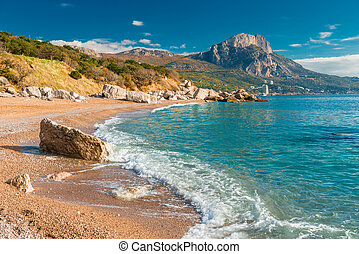 a sea wave on a sandy beach, a seascape in the autumn afternoon