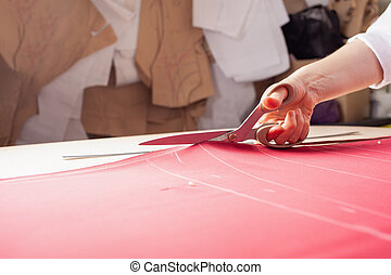 A seamstress woman cuts off the excess red fabric