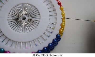 A seamstress woman removes a pin with plastic head from a set of white discs. Dressmaker get a multi-colored needle and put it back