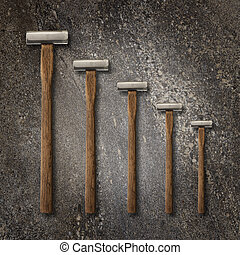 A selection of precision carpentry hammers on a stone backdrop