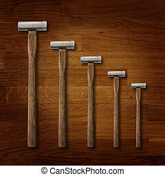 A selection of precision carpentry hammers on a wooden board