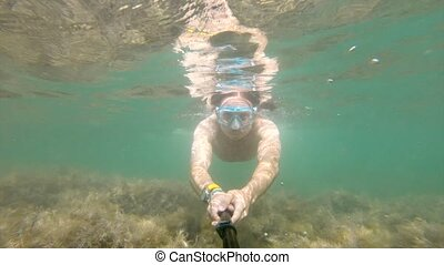 A selfie shot underwater by a Caucasian man sporting a physique floats beautifully underwater. The concept of free diving and recreation on the sea coast or on the ocean.