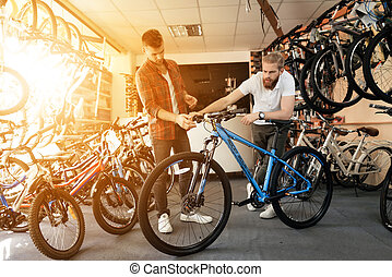 A seller at a bicycle store helps a young buyer choose a new mountain bike.