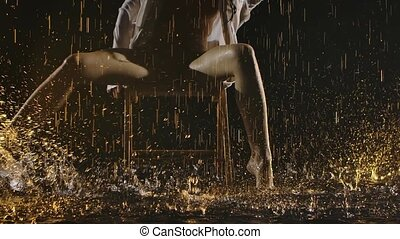 A semi nude young woman in a beige swimsuit and shirt performs smooth movements with her legs while sitting on a chair. Contemporary dance ballerina posing in the pouring rain in a dark studio. Slow motion. Close up.