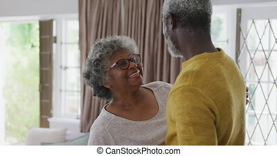A senior African American couple spending time at home together, social distancing and self isolation in quarantine lockdown during coronavirus covid 19 epidemic, dancing in the living room in slow motion