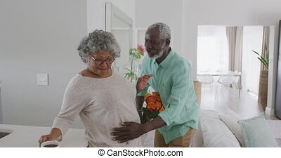 A senior African American couple spending time at home together, social distancing and self isolation in quarantine lockdown during coronavirus covid 19 epidemic, the man giving flowers to the woman