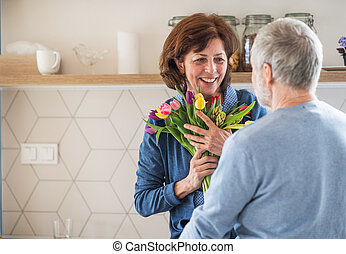 A senior couple in love indoors at home, man giving flowers to woman.