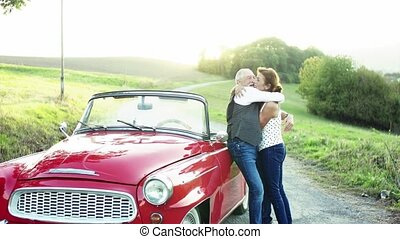 A senior couple in love standing by cabriolet on a road trip...
