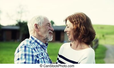 A senior couple in love standing outdoors in nature,...