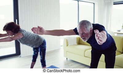 A senior couple indoors at home, doing exercise indoors. - A...