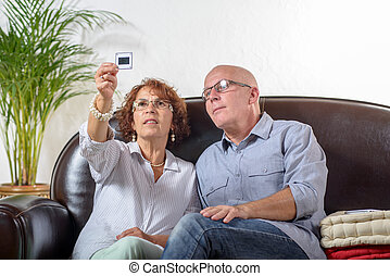 a senior couple looks at a photograph slide