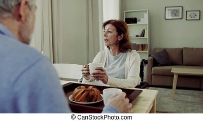 A senior couple sitting at the table at home, having breakfast and talking.