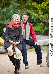 A senior couple Sitting on a tree trunk
